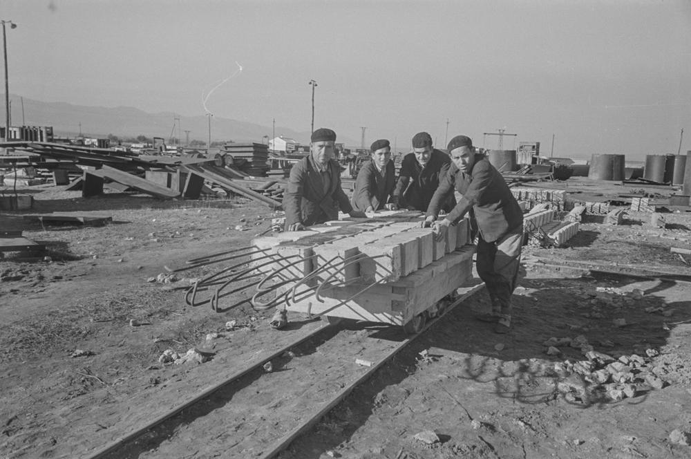 Calvo Sotelo Puertollano. Obreros transportando viga. Fotografía tomada hacia 1952